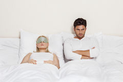Displeased young man with woman sleeping in bed Royalty Free Stock Photo