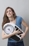 Displeased young woman in pain with weighting scale in hands Stock Photography