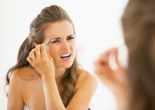 Displeased young woman tweezing eyebrows stock photo