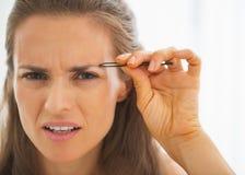 Displeased young woman tweezing eyebrows Stock Image