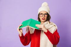 Displeased young woman wearing winter hat isolated over purple background reading book. Portrait of a displeased young woman wearing winter hat isolated over stock image