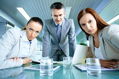 Displeasure. Serious boss with his two employees looking at camera with displeasure Royalty Free Stock Image
