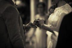 Disponendo anello sul dito alle nozze fotografia stock