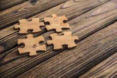 Disponendo un pezzo del puzzle su una vecchia tavola di legno strutturata fotografie stock