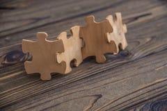 Disponendo un pezzo del puzzle in una fila su una tavola di legno rustica strutturata immagine stock