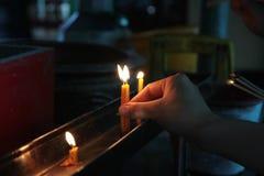 Disponendo una candela accesa sull'altare di Buddha Fotografia Stock Libera da Diritti