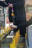 Disponendo una candela accesa sull'altare di Buddha Fotografie Stock Libere da Diritti