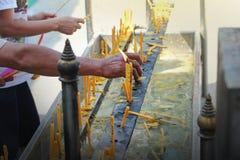 Disponendo una candela accesa sull'altare di Buddha Fotografia Stock