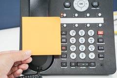 Disponga la nota appiccicosa alta falsa sul telefono del IP in ufficio Fotografia Stock