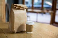 Disponibel kaffekopp och pappers- påse på tabellen i kafé Arkivbilder