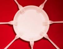 Disponibla plast- plattor och gafflar ligger p? en r?d bakgrund royaltyfri foto