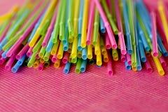 Disponibla plast- sugrör för färgrikt enkelt bruk på rosa yttersida royaltyfri bild
