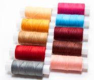 Disposé dans les lignes fils de couture multicolores sur le fond blanc Image stock
