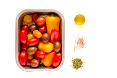 Disposable Aluminum Foil Grilling Tray with Vegetables. Disposable Aluminum foil grilling tray with an assortment of cherry tomatoes and small peppers ready for stock photography
