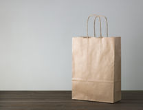 Disposable bag of kraft paper. On a wooden table Stock Photos