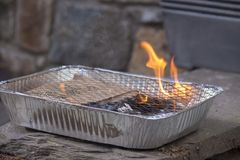 Disposable BBQ with flame ready to cook royalty free stock image