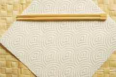 Disposable chopsticks. A pair of disposable bamboo chopsticks on a paper place-mat Royalty Free Stock Photo
