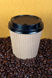 Disposable coffee cup and beans. Photo of a takeaway paper coffee cup with lid on a mixture of arabica and robusta beans Royalty Free Stock Photography