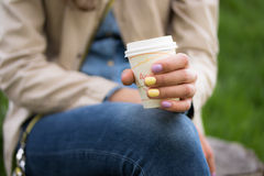 A disposable coffee cup in a female hand closeup. A young girl holds in her left hand with a bright manicure disposable coffee Cup Stock Images