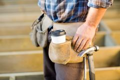 Disposable Coffee Cup And Hammer On Carpenter's Stock Image