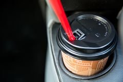 Disposable coffee cup inside car cup holder. Cup made from cardboard with red tube for drinks Stock Images