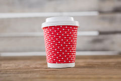 Disposable coffee cup with polka dots on wooden table Royalty Free Stock Photography