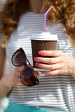 Disposable Coffee Cup and Sunglasses in the hands of woman Stock Photos