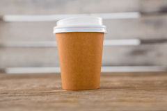 Disposable coffee cup on wooden table Royalty Free Stock Images
