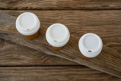 Disposable coffee cups on wooden plank Royalty Free Stock Photos