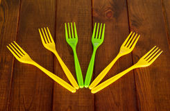 Disposable colored plastic forks on background of dark wood. Royalty Free Stock Photo