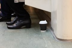 Disposable Cup of coffee is on the floor in the subway train. Disposable Cup of coffee is on the floor in the subway car. The garbage in the city royalty free stock image