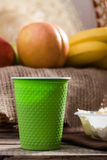Disposable cup and fruit piece. Closeup still life one disposable green cup blurred peaches and bananas lying on brown sackcloth on rustic wooden background Stock Photo