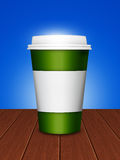 Disposable cup with lid standing on desk Royalty Free Stock Image