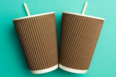 Disposable cups for hot drinks on a turquoise backgrounds. Paper cups.  royalty free stock photography