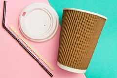 Disposable cups for hot drinks wand and tube on a geometric pink and turquoise backgrounds. Paper cups set.  royalty free stock photography