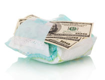 Disposable diaper and money close up isolated on white. Royalty Free Stock Image