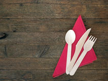 Disposable eco-friendly wooden cutlery and re serviette on rusti Royalty Free Stock Images