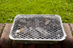 Disposable foil BBQ on wall Stock Photo