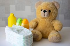 Disposable nappies, baby accessories and teddy bear royalty free stock image