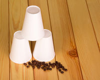 Disposable paper cups and coffee beans on background light wood. Royalty Free Stock Image