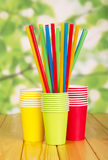 Disposable paper cups and straws on abstract green. Royalty Free Stock Photography