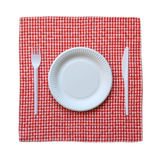 Paper plate on a checkered cloth. Disposable paper plate on a checkered cloth isolated on a white background Stock Photo