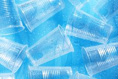 Disposable plastic cups with water drops. On a blue background Stock Image