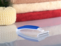 Disposable Plastic Razor. Plastic disposable shaver with a pile of towels in the back with reflection (Selective Focus, Focus on the front of the shaver Royalty Free Stock Photography