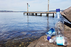 Disposable plastic water bottles. Sitting on a rock by a clean lake Stock Image