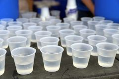 Disposable plastic water cups on table royalty free stock image
