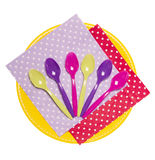 Disposable plate, colorful spoons and napkins isolated on white. Stock Photos