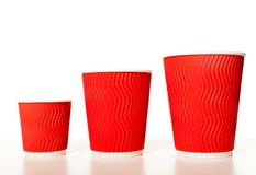 Set of paper cups. Disposable red paper coffee cups  of different sizes standing in a row on a white background, mockup for design for espresso, cappuccino Stock Photos