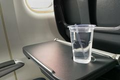 Disposable refreshing mineral water on table in air plane cabin Stock Photos