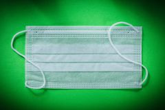 Disposable sterile face mask on green background Royalty Free Stock Photos
